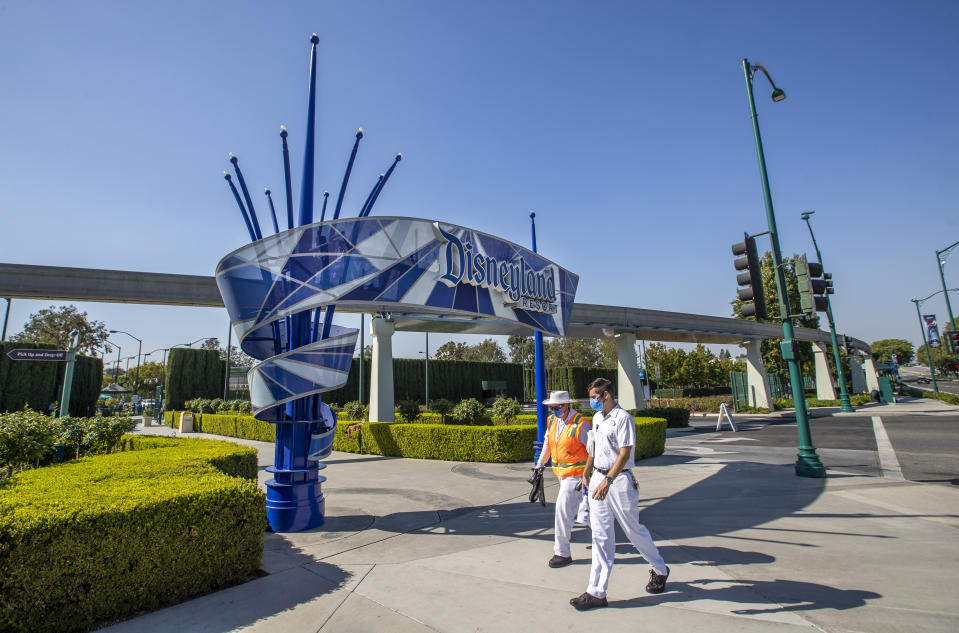 ANAHEIM, CA - SEPTEMBER 30: Employees walk past the entrance to Disneyland Park on Wednesday, Sept. 30, 2020 in Anaheim, CA. After suffering losses for months due to Gov. Newsoms mandatory coronavirus shut-down, Disney says it will lay off 28,000 employees across its parks, experiences and consumer products segment.(Allen J. Schaben / Los Angeles Times via Getty Images)