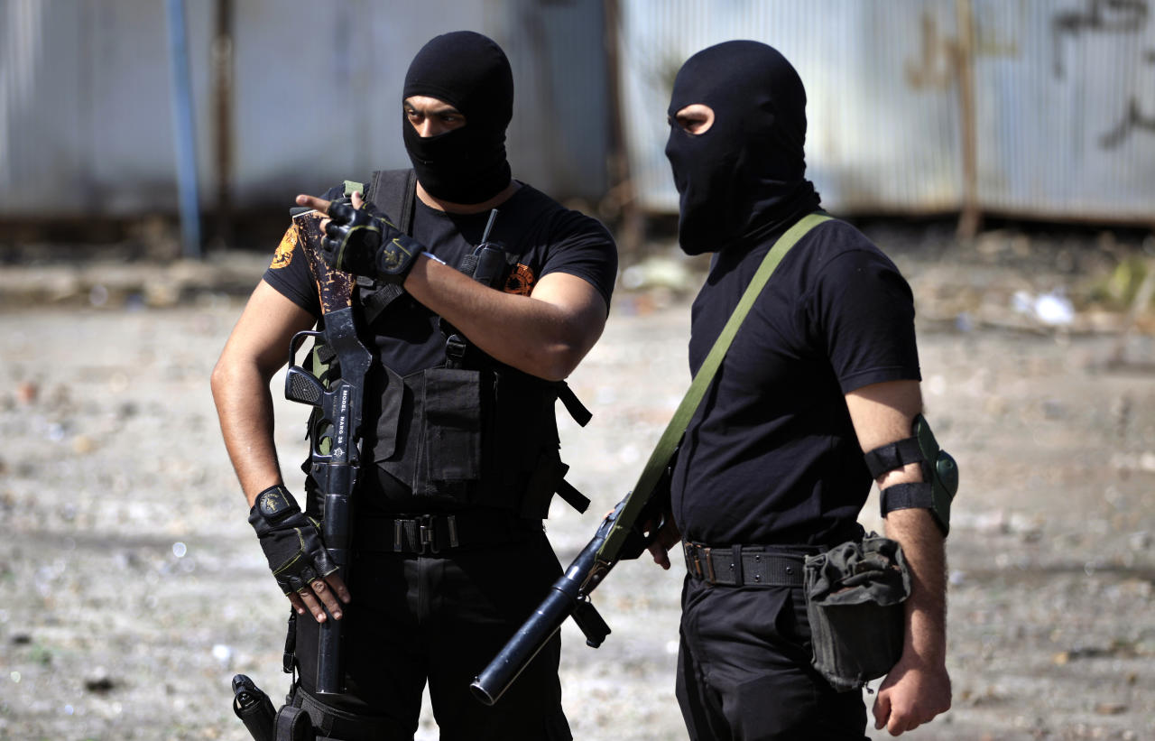Two Egyptian police officers wear masks as they stand guard during clashes with protesters, not seen, near the state security building in Port Said, Egypt, Wednesday, March 6, 2013. Clashes between protesters and police have broken out in this restive Egyptian port city despite efforts by the military to separate the two sides. (AP Photo/Khalil Hamra)