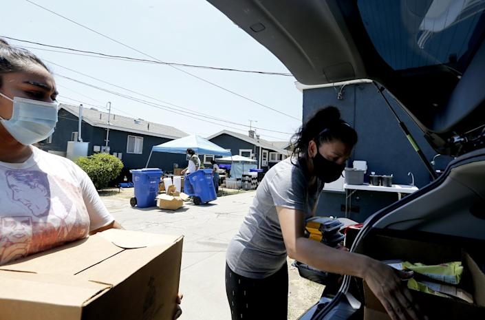 Gabriella Barrera, left, helps load boxes of groceries into the car of a volunteer driver.