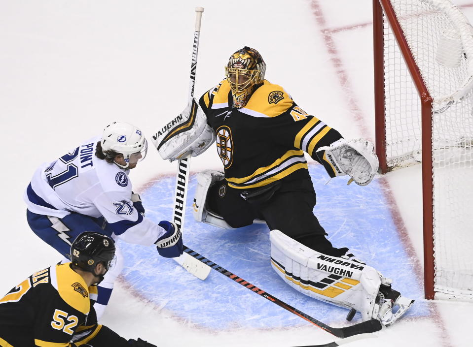 Boston Bruins goaltender Tuukka Rask (40) makes a pad save against Tampa Bay Lightning center Brayden Point (21) as Bruins center Sean Kuraly (52) looks on during the third period of an NHL hockey playoff game Wednesday, Aug. 5, 2020 in Toronto. (Nathan Denette/The Canadian Press via AP)