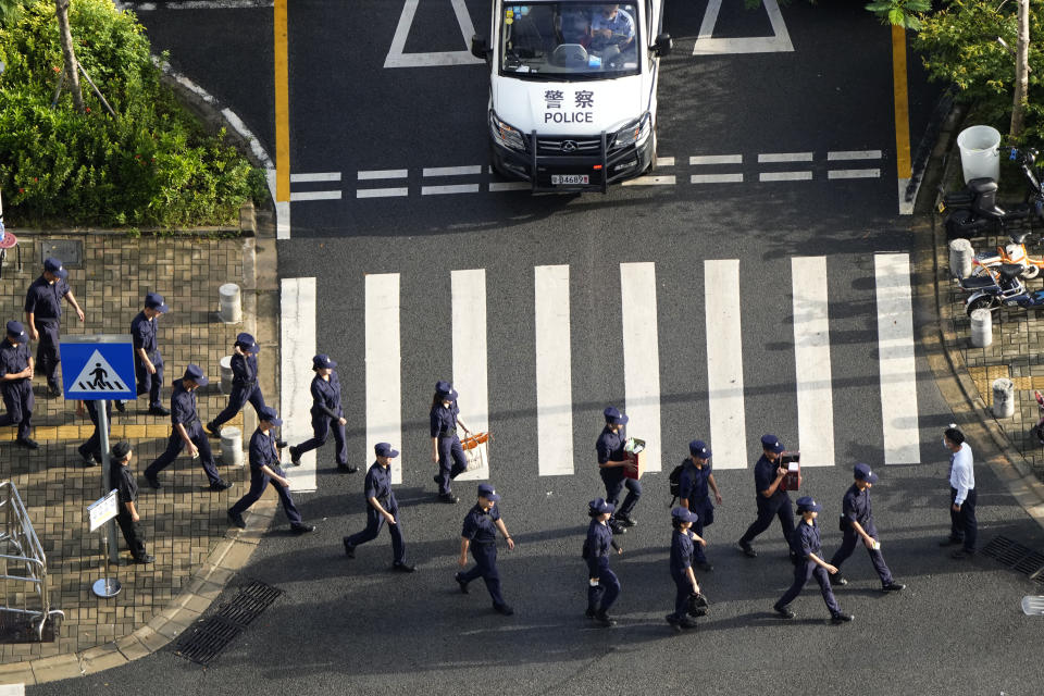 Security personnel march to their duty outside the Evergrande headquarters in Shenzhen, China, Friday, Sept. 24, 2021. Seeking to dispel fears of financial turmoil, some Chinese banks are disclosing what they are owed by the real estate developer that is struggling under $310 billion in debt, saying they can cope with a potential default.(AP Photo/Ng Han Guan)