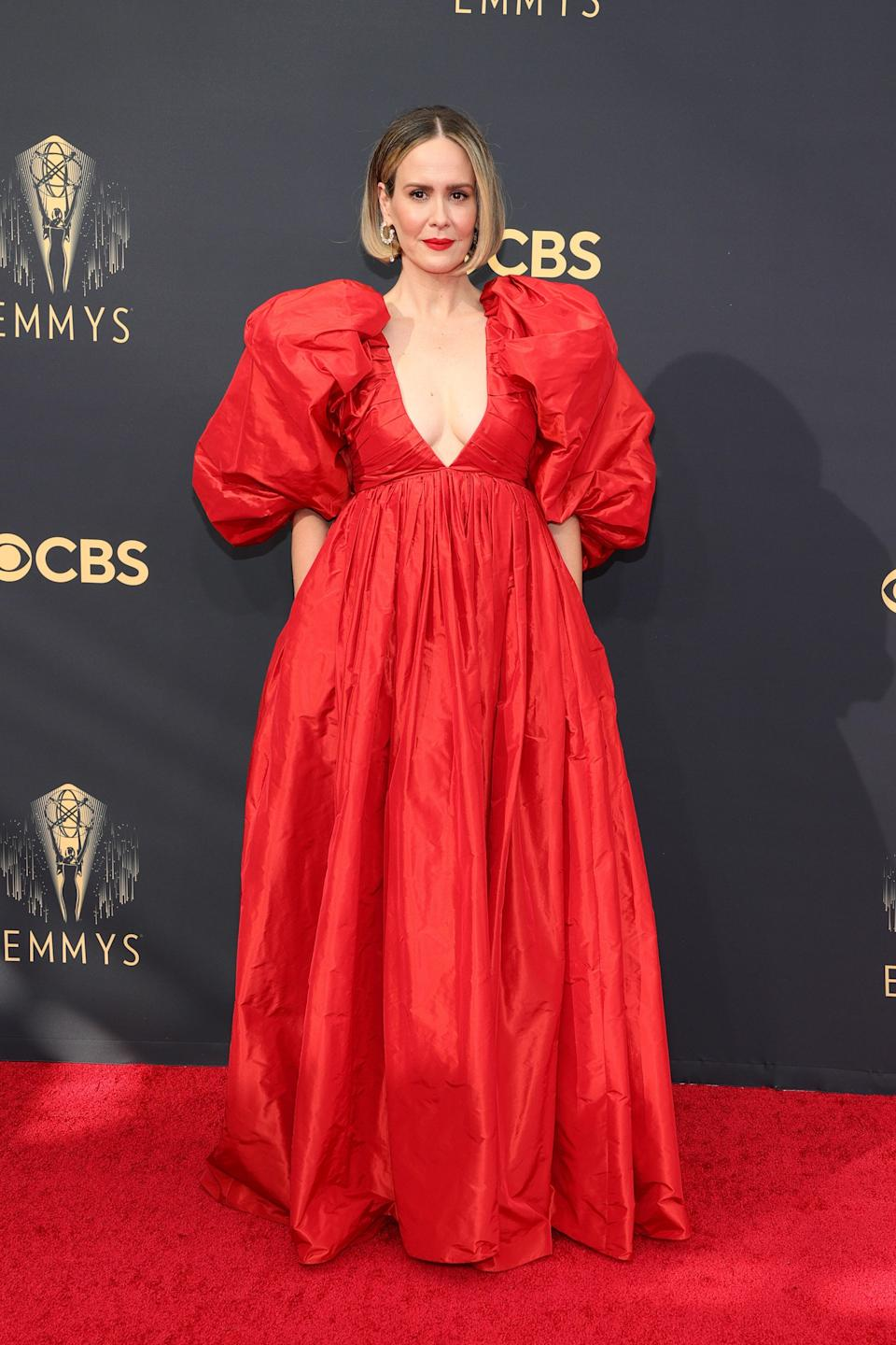 Beanie's <em>American Crime Story</em> costar matched the carpet in her scarlet Carolina Herrera gown with a deep V-neck, massive puffed sleeves, and a perfectly paired red lip.