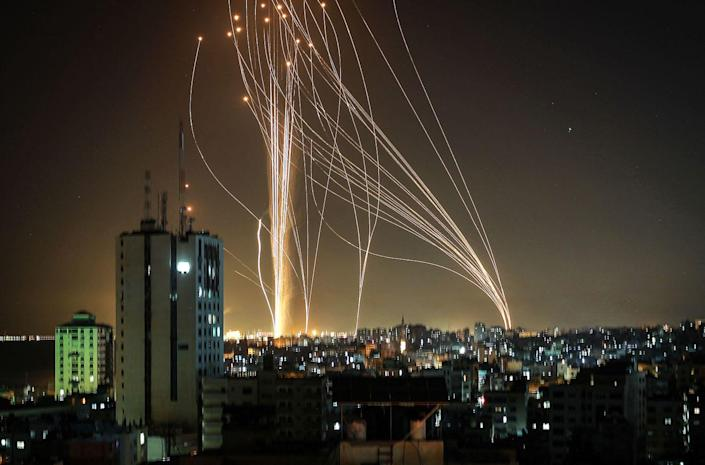 Rockets are launched in the night sky above buildings