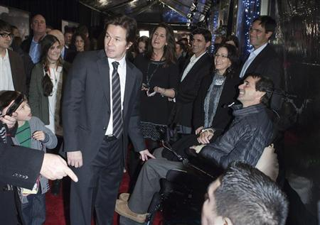 """Cast member Mark Wahlberg greets a man in a wheelchair during the premiere of the movie """"Lone Survivor"""" in New York"""