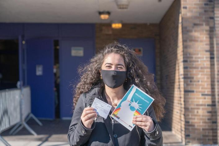 "A woman displays her vaccination card and the ""IGotTheShotNYC"" banner after exiting the NYC Health Department Vaccine Hub at Hillcrest High School in Queens"