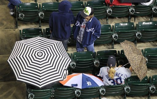 Baseball fans wait out a rain delay before a baseball game between the Minnesota Twins and the Detroit Tigers at Comerica Park in Detroit, Friday, Sept. 21, 2012. (AP Photo/Carlos Osorio)