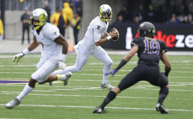 Oregon quarterback Marcus Mariota, center, looks to pass as Washington's Gregory Ducre (18) defends in the first half of an NCAA college football game, Saturday, Oct. 12, 2013, in Seattle. (AP Photo/Elaine Thompson)