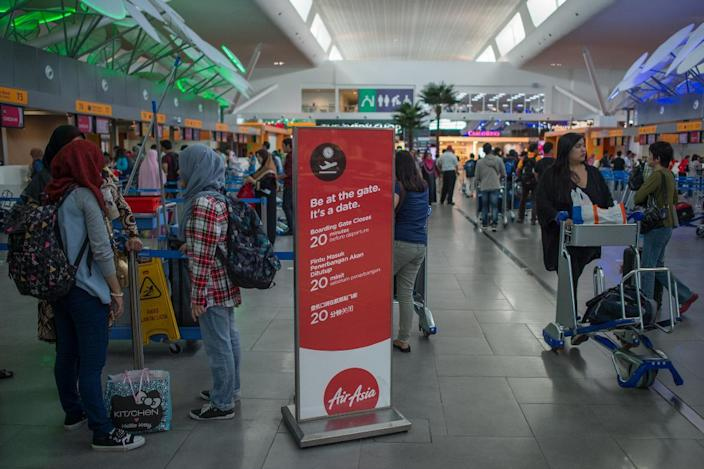 Passengers stand near an AirAsia information board at the low-cost carrier Kuala Lumpur International Airport 2 (KLIA2) in Sepang, on January 10, 2015 (AFP Photo/Mohd Rasfan)