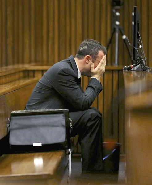 With a bucket on the floor nearby, Oscar Pistorius covers his face with his hands as he listens to cross questioning about the events surrounding the shooting death of his girlfriend Reeva Steenkamp, in court during his trial in Pretoria, South Africa, Monday, March 10, 2014. Pistorius vomited in the dock and retched repeatedly and loudly as he heard graphic details of the injuries sustained by Steenkamp, who he fatally shot on Feb. 14, 2013. (AP Photo/Siphiwe Sibeko, Pool)