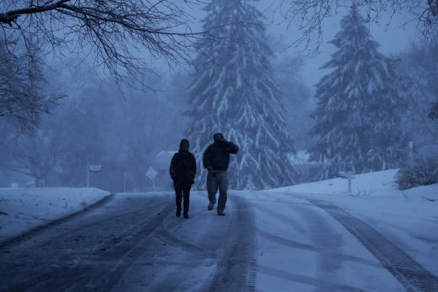 <p>A family walks down a snowy street during a winter storm, Friday, March 2, 2018, in Marple Township, Pa. (Photo: Matt Slocum/AP) </p>