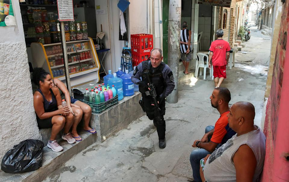 A policeman takes position during an operation against drug dealers in Jacarezinho slum in Rio de Janeiro, Brazil May 6, 2021. REUTERS/Ricardo Moraes     TPX IMAGES OF THE DAY