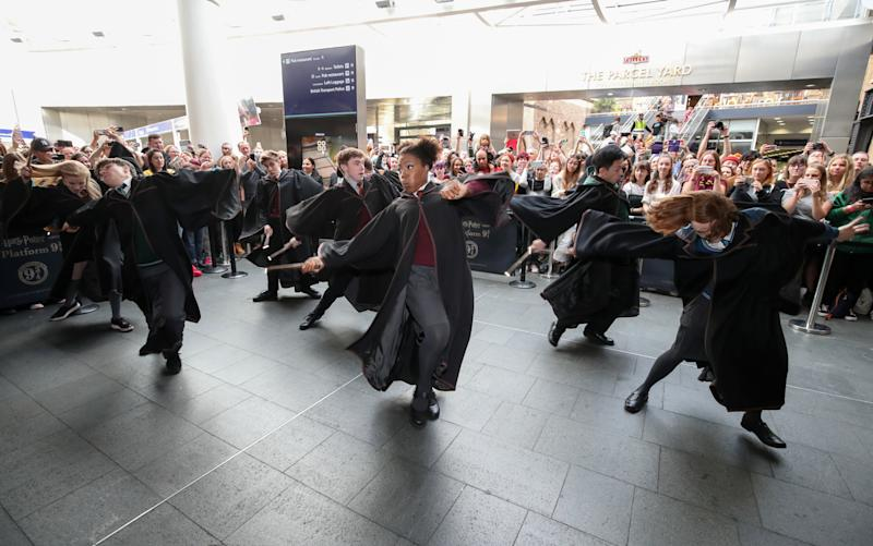 Cast members from Harry Potter and the Cursed Child perform at London Kings Cross Station as Harry Potter fans gather to watch as the Hogwarts Express appears on the departure board at London King's Cross during Back to Hogwarts Day. (Photo by Chris Radburn/PA Images via Getty Images)