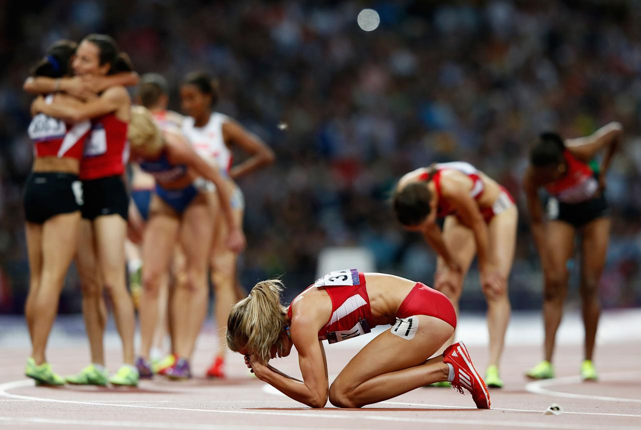 LONDON, ENGLAND - AUGUST 10:  Morgan Uceny of the United States reacts after falling as athletes celebrate behind her during the Women's 1500m Final on Day 14 of the London 2012 Olympic Games at Olympic Stadium on August 10, 2012 in London, England.  (Photo by Jamie Squire/Getty Images)