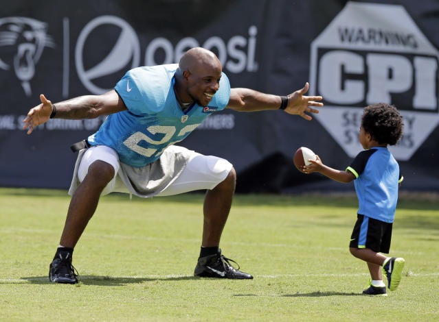 Carolina Panthers' Josh Thomas, left, reaches out to hug his son, Dallas, 2, right, after an NFL football practice at their training camp in Spartanburg, S.C., Tuesday, July 29, 2014. (AP Photo/Chuck Burton)