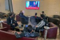People watch Libya's newly-elected Prime Minister Abdulhamid Dbeibeh speaks on a TV screen at a cafe in Misrata