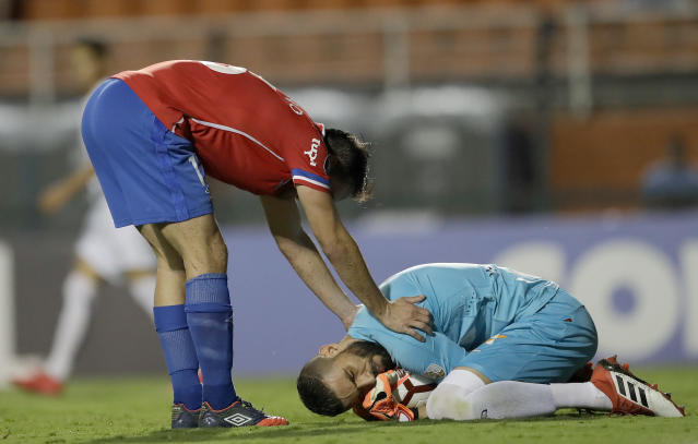 Paulo Matias Zunino of Uruguay's Nacional, left, holds goalkeeper Vanderlei of Brazil's Santos after a save, during a Copa Libertadores soccer match in Sao Paulo, Brazil, Thursday, March 15, 2018. (AP Photo/Andre Penner)