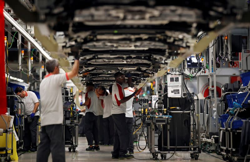 Workers assemble vehicles on the assembly line of the SEAT car factory in Martorell