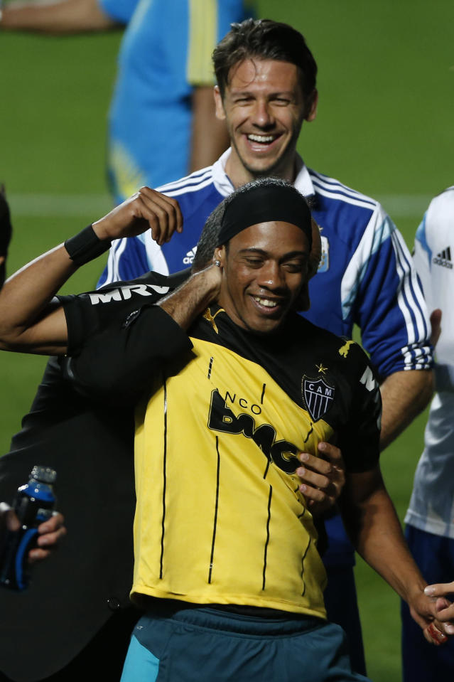 Argentina's Martin Demichelis, top, smiles wide as a security guard escorts a fan resembling Brazilian soccer player Ronaldinho, off the pitch at the end of a training session at Independencia Stadium in Belo Horizonte, Brazil, Wednesday, June 11, 2014. Argentina will play in group F of the Brazil 2014 soccer World Cup. (AP Photo/Bruno Magalhaes)