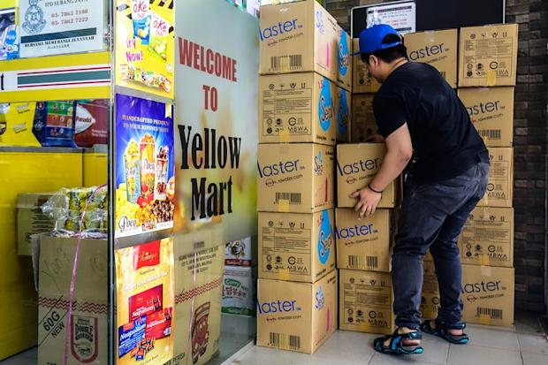 A worker arranges boxes of mineral water bottles for sale at a mart in Subang Jaya March 8, 2019.