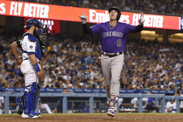 Colorado Rockies' Josh Fuentes, right, celebrates as he scores after hitting a solo home run as Los Angeles Dodgers catcher Russell Martin stands at the plate during the seventh inning of a baseball game Saturday, Sept. 21, 2019, in Los Angeles. (AP Photo/Mark J. Terrill)