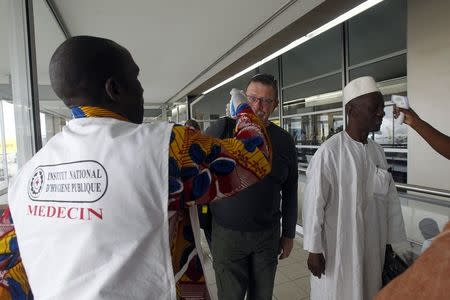 Health workers take passengers' temperatures infrared digital laser thermometers at the Felix Houphouet Boigny international airport in Abidjan August 13, 2014.REUTERS/Luc Gnago
