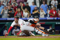 Philadelphia Phillies' Bryce Harper, left, scores the game-winning run past Baltimore Orioles catcher Austin Wynns on a two-run triple by J.T. Realmuto during the 10th inning of an interleague baseball game, Tuesday, Sept. 21, 2021, in Philadelphia. (AP Photo/Matt Slocum)