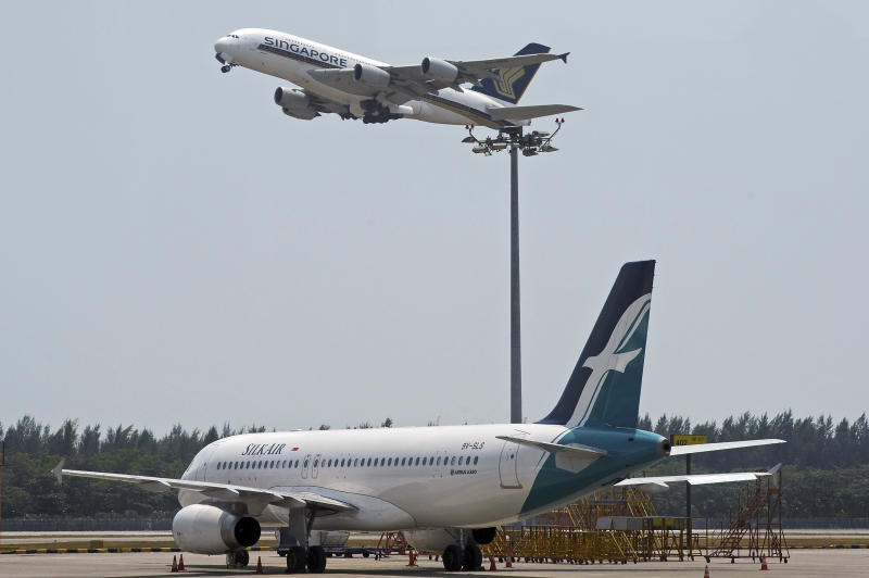 """In this Feb. 10, 2014, photo, a Singapore Airlines Airbus A380, top, takes off at Singapore's Changi Airport as an Airbus A320 from its subsidiary airline, Silkair sits on the tarmac, bottom. Drones buzzing around Singapore's Changi Airport have caused the delay or diversion of 63 flights in the past week, triggering an official investigation and raising questions about the motives of the offenders. Regulators said Tuesday, June 25, 2019, that 18 flights at the airport were delayed and seven were diverted the night before """"due to bad weather and unauthorized drone activities(AP Photo/Joseph Nair)"""