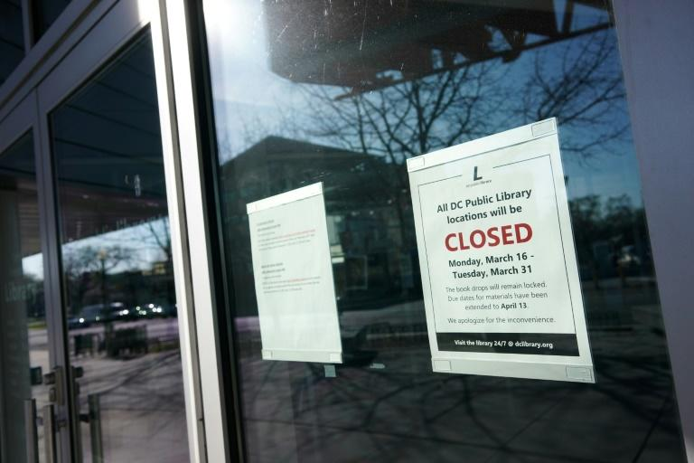 "A ""closed"" sign is viewed on the door of the Tenley/Friendship DC Public Library on March 16, 2020, in Washington, DC"