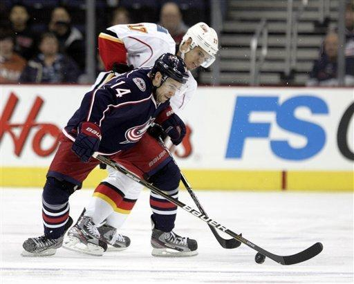 Columbus Blue Jackets' Grant Clitsome, left, and Calgary Flames' Rene Bourque work for the puck in the first period of an NHL hockey game in Columbus, Ohio, Tuesday, Dec. 27, 2011. (AP Photo/Paul Vernon)
