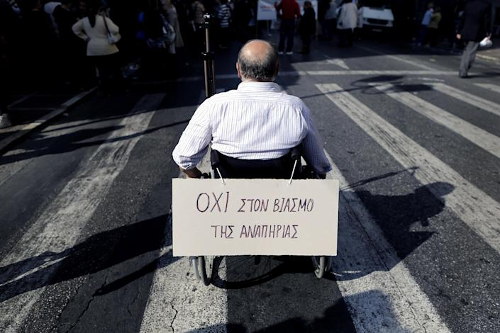 """A man on a wheelchair with a placard reading in Greek """"No to the rape of special needs"""" takes part in an anti-austerity demonstration in central Athens, on Thursday, Oct. 31, 2013. Athens' streets were clogged by four separate protests Thursday ahead of an inspection due to start next week by bailout lenders who are demanding fresh cuts. (AP Photo/Petros Giannakouris)"""