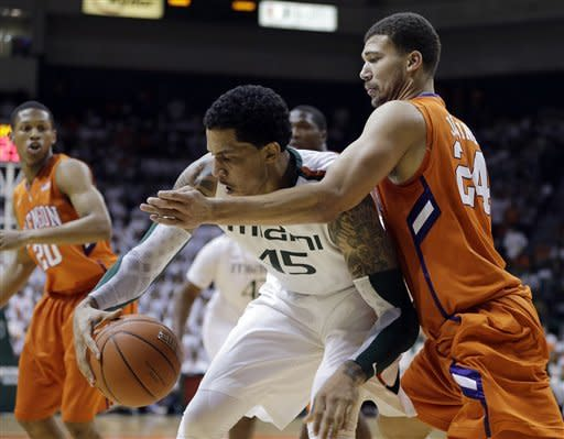Clemson's Milton Jennings (24) tries to steal the ball from Miami's Julian Gamble (45) during the first half of a NCAA college basketball game in Coral Gables, Fla., Saturday, March 9, 2013. (AP Photo/J Pat Carter)