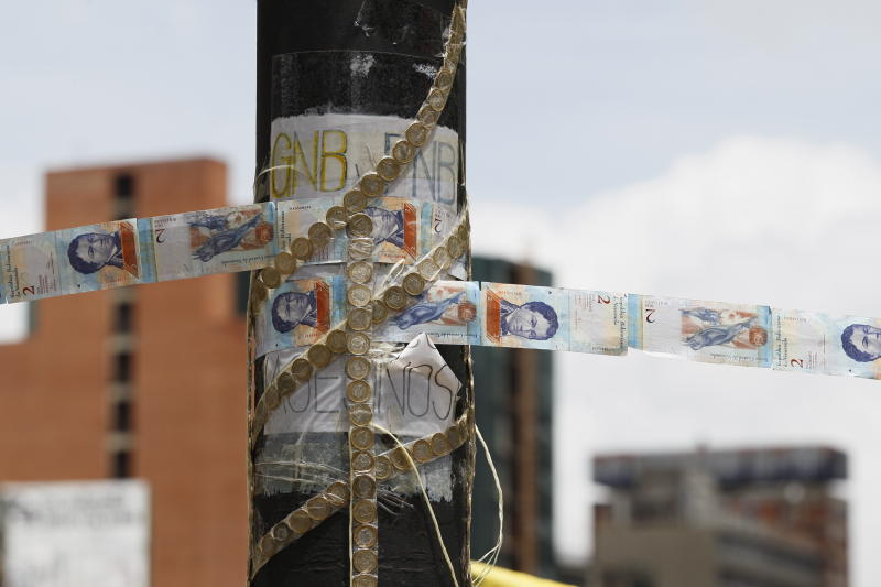 FILE - In this July 20, 2017 file photo, devalued Bolivar bank notes and coins, taped together, serve as makeshift rope at a roadblock set up by anti-government protesters in Caracas, Venezuela. Forced to meet interest payments on the few remaining loans and bonds the government hasn't yet defaulted on, the government must finance its huge budget deficit by printing even more bolivars, further accelerating prices. (AP Photo/Ariana Cubillos, File)