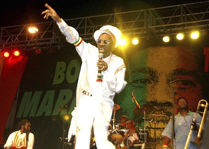 Bunny Wailer performs in front of a backdrop featuring Bob Marley's face