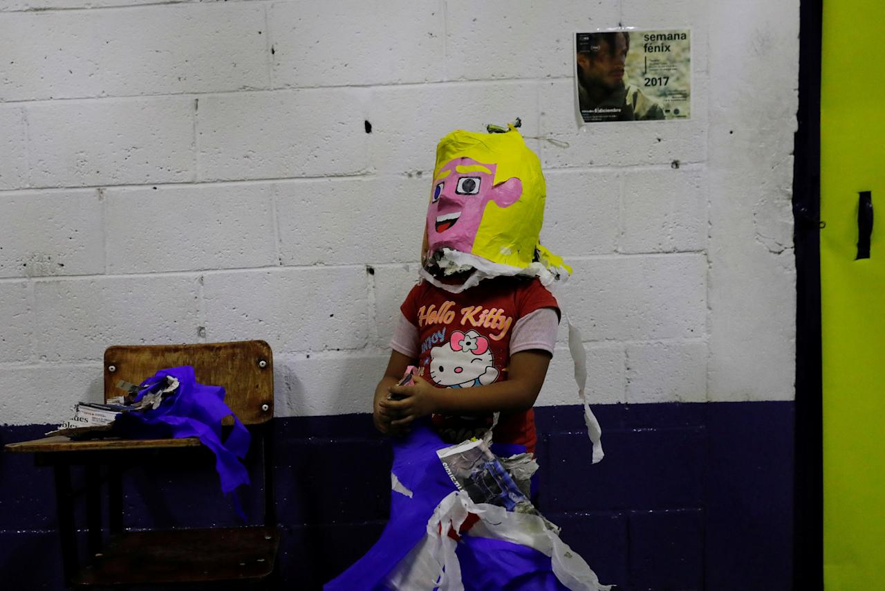 "A child wears the head of a pinata resembling U.S. President Donald Trump during a pre-Christmas ""Posada"" celebration organised by deported immigrants in Mexico City, Mexico December 16, 2017. REUTERS/Carlos Jasso"