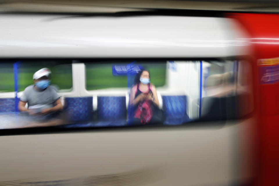 Two people wearing protective masks sit two seats apart on a moving London underground train as the UK continues to recover from the coronavirus pandemic.