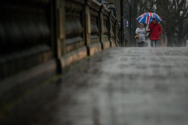 People shield themselves from heavy rain as they walk in Worcester (Jacob King/PA)