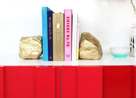 """<p>A bookshelf full of best-sellers deserves a little bling. Open a new chapter to style with these decked-out bookends made from humble rocks <a href=""""http://www.bobvila.com/slideshow/10-unexpected-uses-for-spray-paint-46231"""" title=""""uses for spray paint"""">spray painted</a> in a metallic hue. Attach cork pads to the base of each bookend to give your shelf a scratch-proof, storybook ending!<i>Photo: <a href=""""http://www.designlovefest.com/2013/04/make-it-33/"""" title=""""http://www.designlovefest.com/2013/04/make-it-33/"""">designlovefest.com</a><br /></i><b>RELATED: <a href=""""http://www.bobvila.com/slideshow/10-novel-diys-for-a-better-bookshelf-49374"""" title=""""http://www.bobvila.com/slideshow/10-novel-diys-for-a-better-bookshelf-49374"""">10 Novel DIYs for a Better Bookshelf</a></b></p>"""
