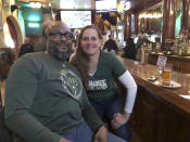 In this May 8, 2019 photo, longtime Bucks fans and season-ticket holders, Rod Johnson and his wife, Therese, both from Milwaukee, pose for a photo at a bar near the stadium before last Wednesday's game. (AP Photo/Ivan Moreno)