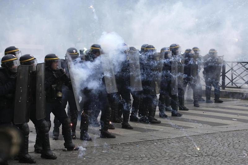 Riot police officers face youths during the May Day demonstration, seized on by anti-Le Pen protesters (AP)