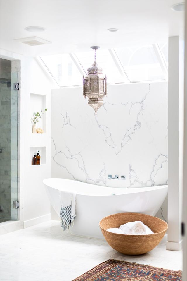 "<p><a href=""https://www.housebeautiful.com/design-inspiration/a26144307/marble-countertops/"" target=""_blank"">Marble countertops</a> are super common, but a marble wall!? That's super fresh! Paired with that uniquely rounded bathtub, Jane's master bathroom gives major spa vibes!</p>"