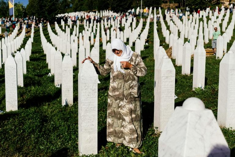 A Bosnian woman mourns at the grave of a relative at the Potocari Memorial Center near the town of Srebrenica, where almost 8,000 Muslims men and boys were killed in July 1995