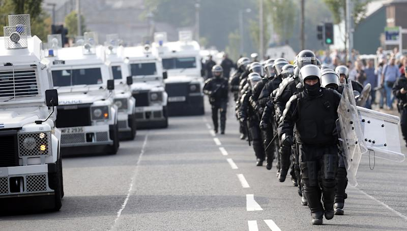 Riot police patrol the Ardoyne area of north Belfast, Northern Ireland, Friday, July 12, 2013. A large security operation swung into place as a controversial Protestant Orange Order march passed the Catholic Ardoyne area. (AP Photo/Peter Morrison)