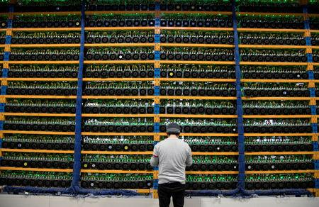 FILE PHOTO: A worker checks the fans on miners, at the cryptocurrency farming operation, Bitfarms, in Farnham, Quebec, Canada, February 2, 2018.  REUTERS/Christinne Muschi/File Photo