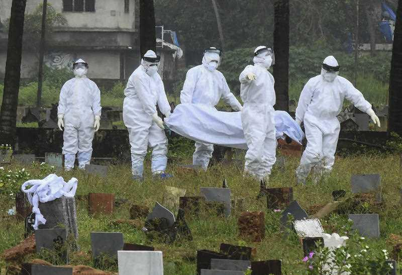 People in protective suits prepare to cremate the body of a 12-year-old boy died of the Nipah virus in Kozhikode, Kerala state, India.