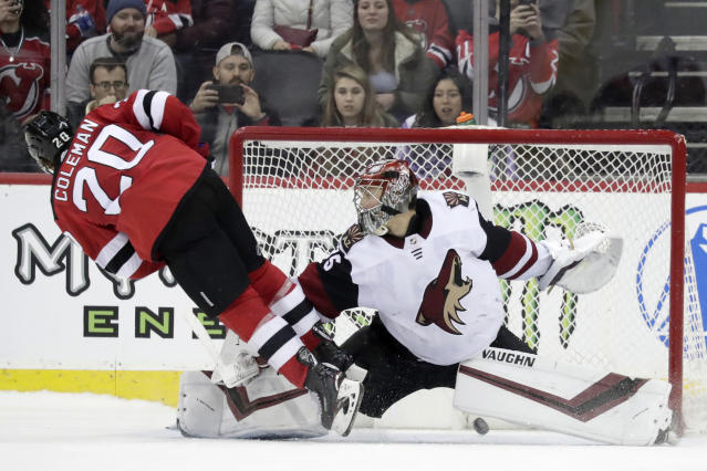 New Jersey Devils center Blake Coleman (20) trips over Arizona Coyotes goaltender Darcy Kuemper (35) while scoring during a shootout in an NHL hockey game, Saturday, March 23, 2019, in Newark, N.J. The Devils on 2-1 in a shootout. (AP Photo/Julio Cortez)