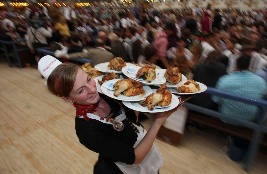 A waitress carries grilled chicken at a beer tent. Over 500,000 units of chicken were consumed at the 2010 Oktoberfest.
