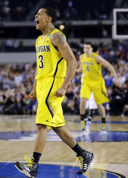 FILE - In this March 29, 2013, file photo, Michigan's Trey Burke (3) reacts after making a three-point basket in the final seconds of the second half of a regional semifinal game against Kansas in the NCAA college basketball tournament in Arlington, Texas. Burke, the sophomore point guard who led Michigan to the Final Four, has been selected The Associated Press' college basketball player of the year on Thursday, April 4, 2013. (AP Photo/David J. Phillip, File)