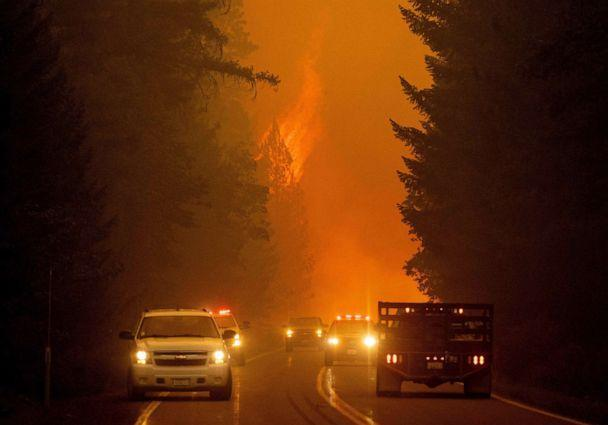 PHOTO: Firefighters monitor the scene as flames from the Dixie fire jump across highway 89 near Greenville, Calif., Aug. 3, 2021. (Josh Edelson/AFP via Getty Images)