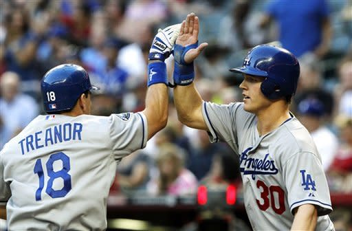 Los Angeles Dodgers' Matt Treanor (18) high-fives Jerry Sands (30) after Treanor's two-run home run during the second inning of a baseball game against the Arizona Diamondbacks, Monday, May 21, 2012, in Phoenix. (AP Photo/Ross D. Franklin)