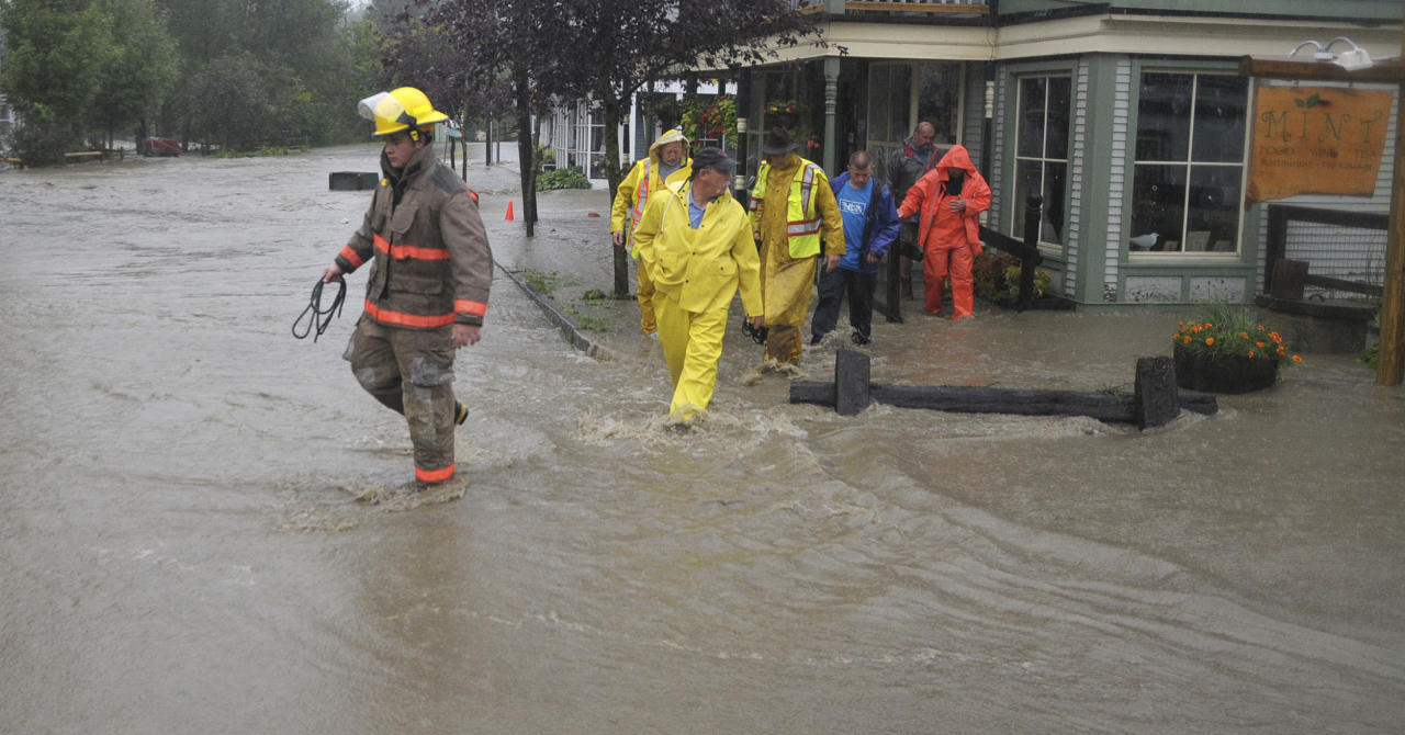 Waitsfield firefighters and rescuers wade through a street flooded by rain from Tropical Storm Irene after assisting residents in a building in Waitsfield, Vt., Sunday, Aug. 28, 2011. (AP Photo/Sandy Macys)